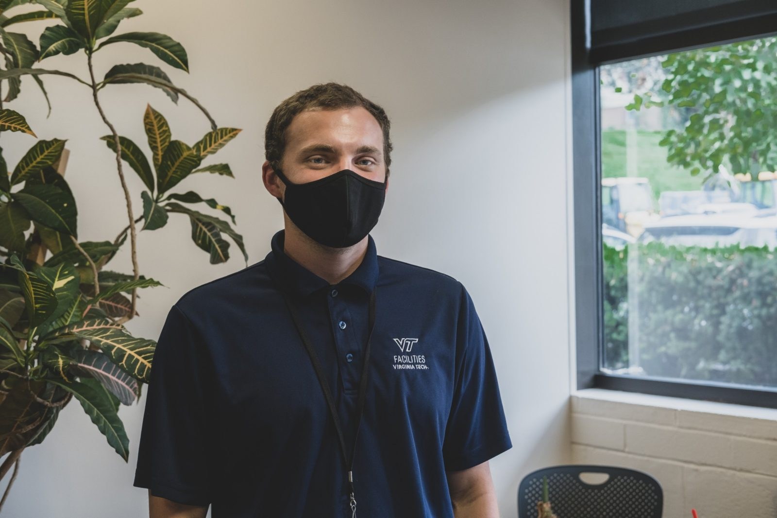 An employee wears a black mask and a dark blue housekeeping shirt.