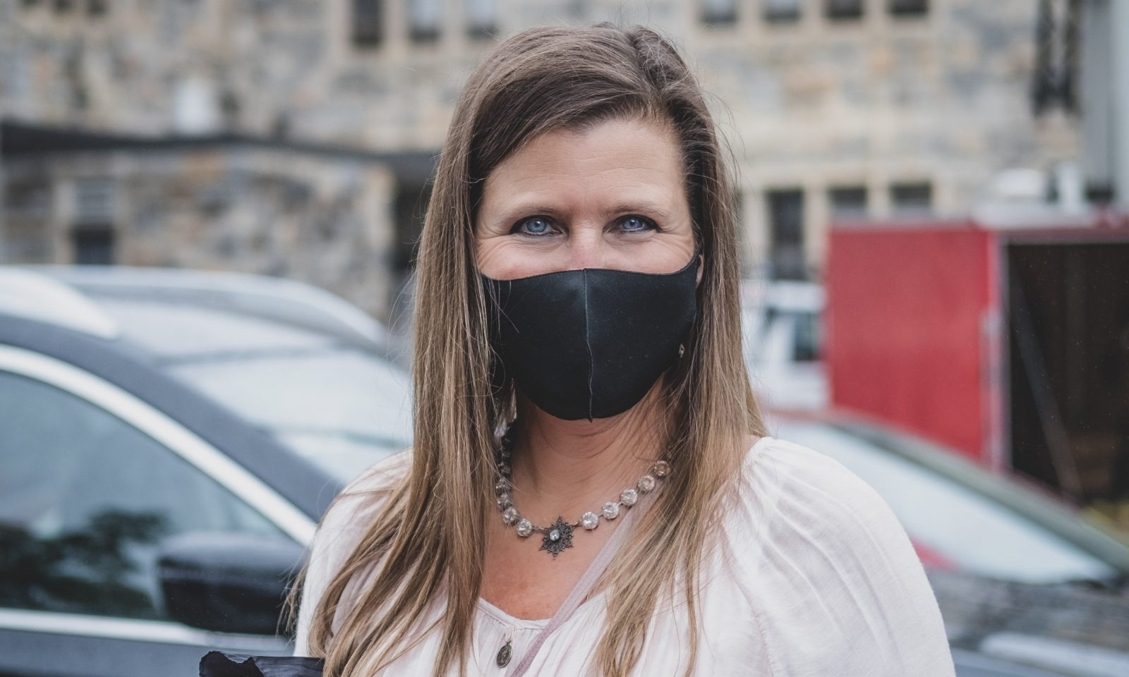 Portrait of someone in a black mask in front of a building and cars. She has blue eyes and long brown hair, wearing a light pink shirt.
