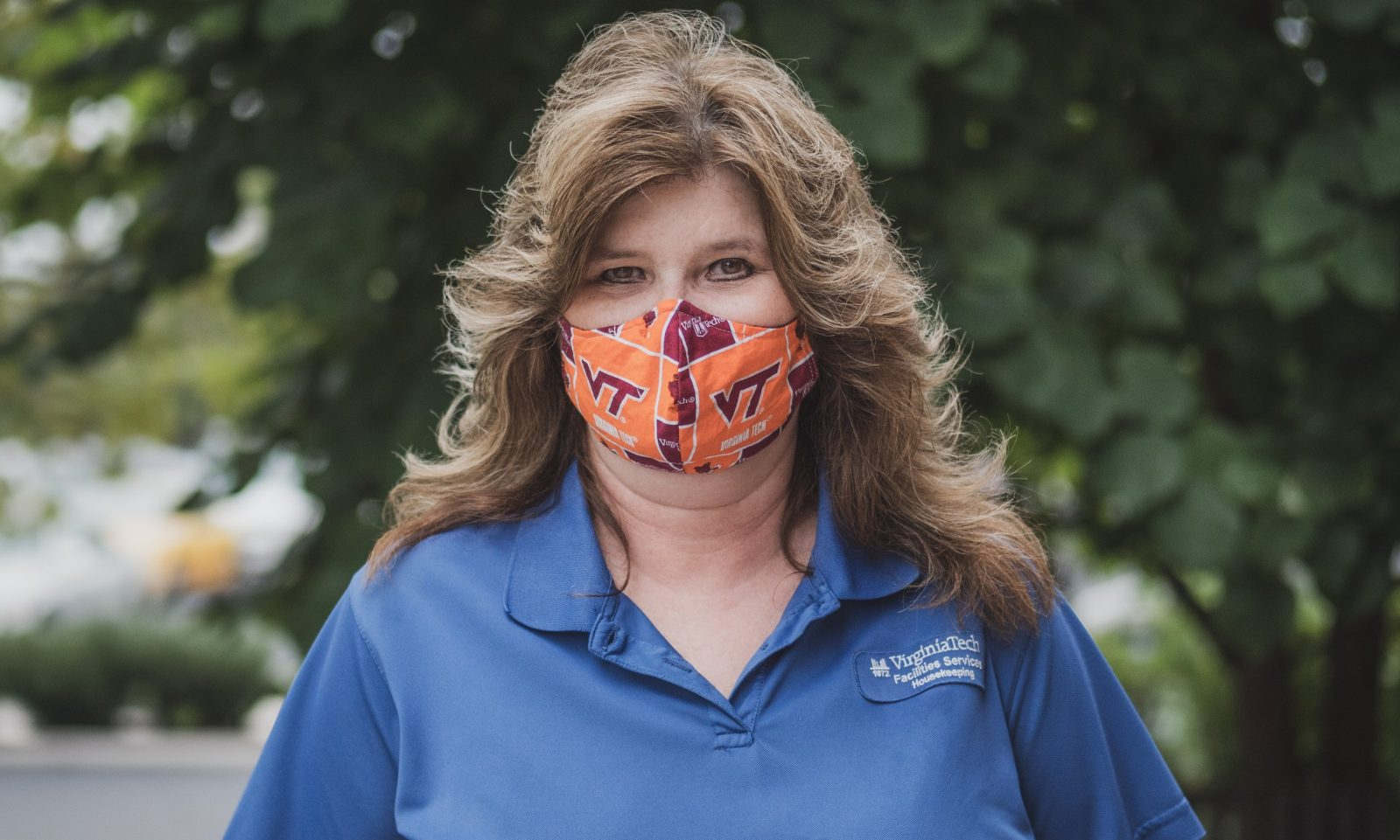 Susan Hypes, Housekeeper, standing outside wearing a VT orange and maroon mask and a blue housekeeping shirt.